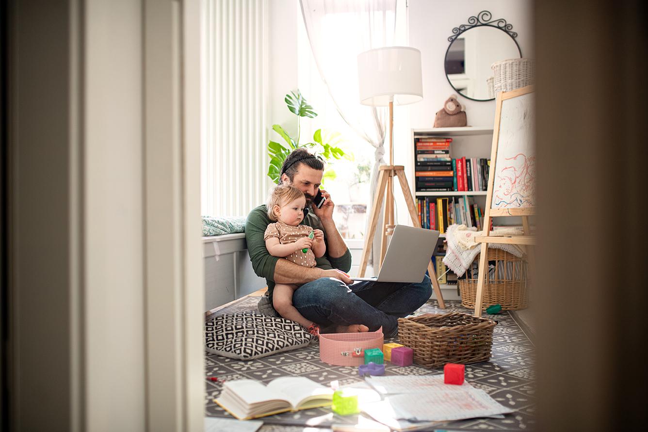 Pappa jobbar hemifrån med småbarn i famnen.